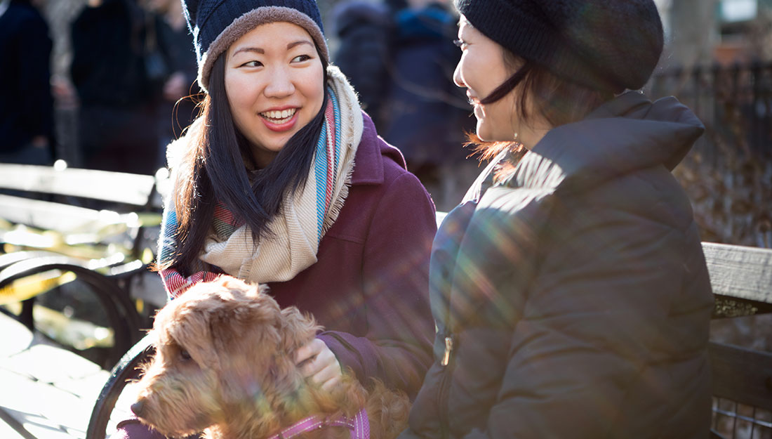 women with dog talking in park