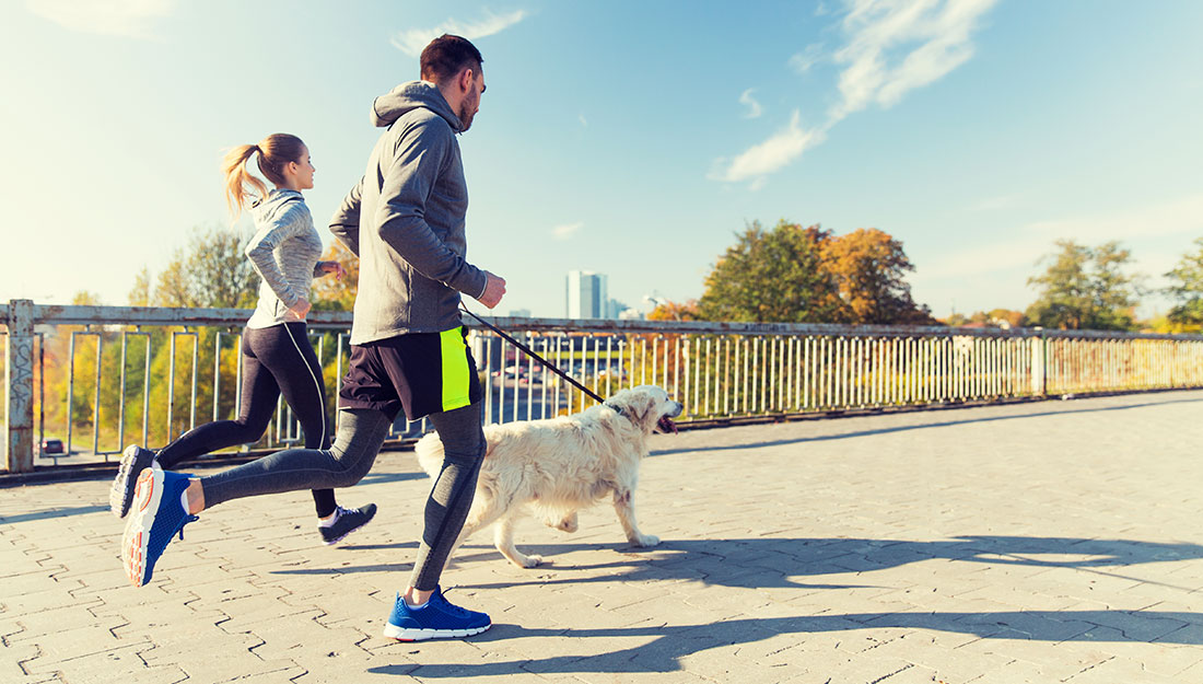 Couple running with dog