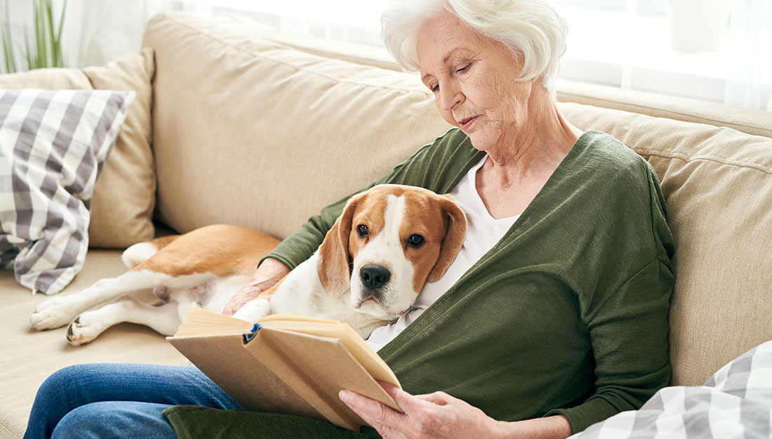 Woman reading with dog on lap