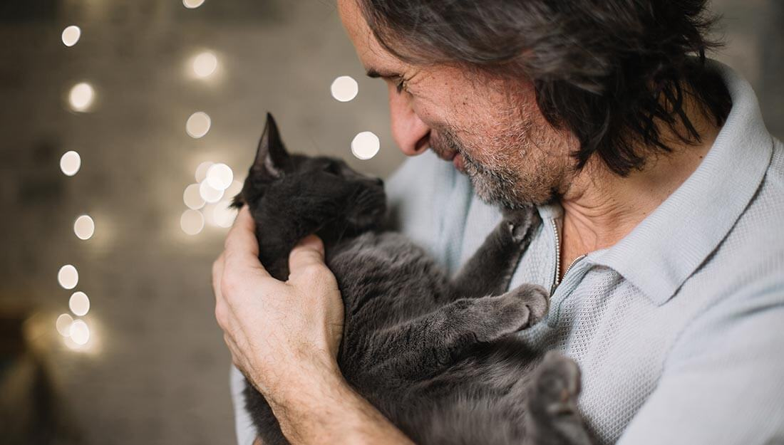 Man smiling down at a grey cat he's holding