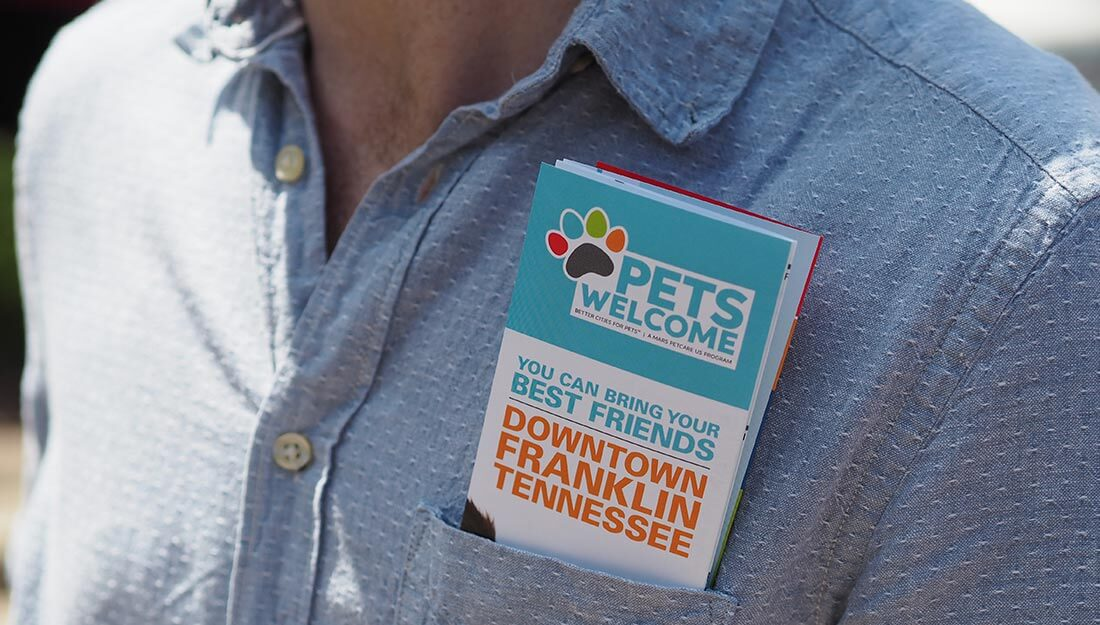 A Pets Welcome map sticking out of someone's pocket