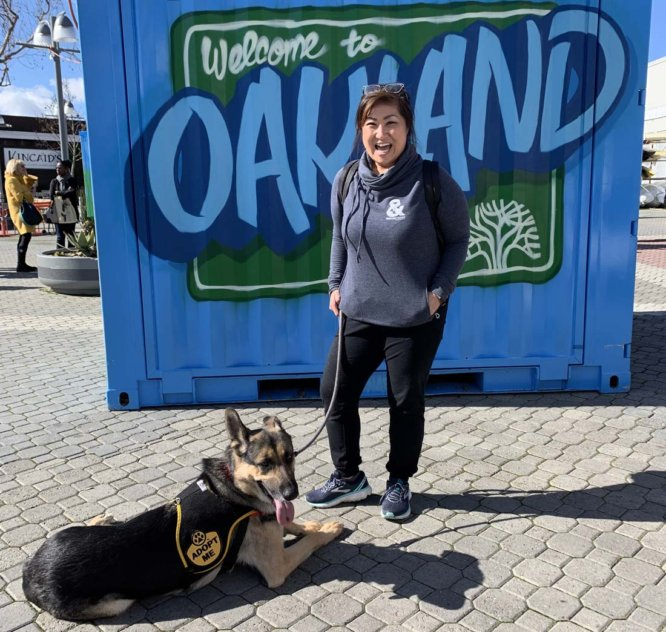 """Dog and dog walker by """"Welcome to Oakland"""" sign."""