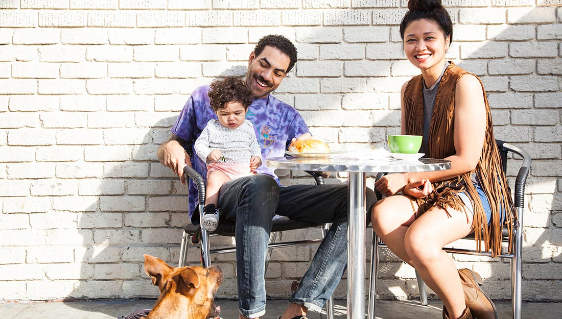 Family at outdoor cafe with dog