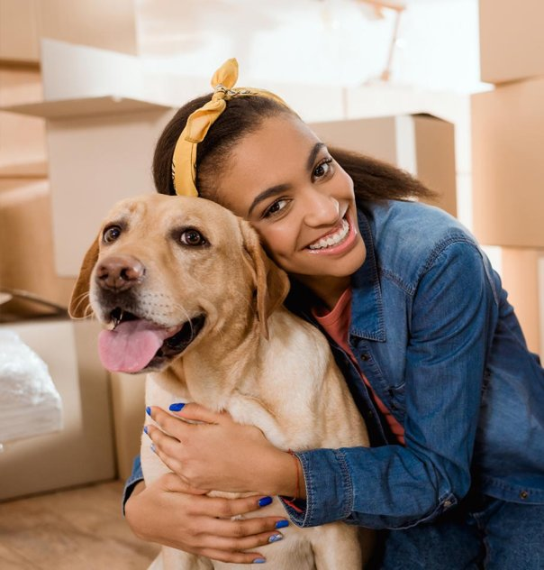 woman with dog in apartment with moving boxes