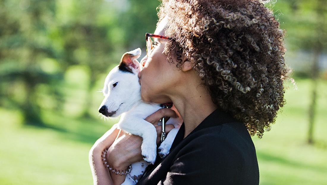 woman kissing puppy at park